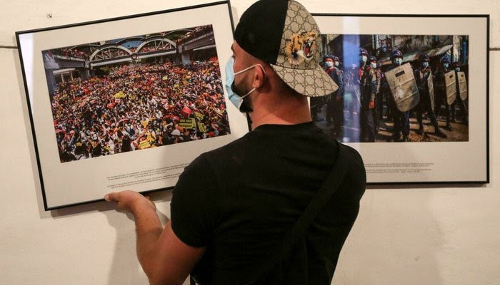 A worker hangs photos for the exhibition Anonymous photographer in Myanmar ahead of the Visa pour lImage international photojournalism festival in Perpignan, France. AFP